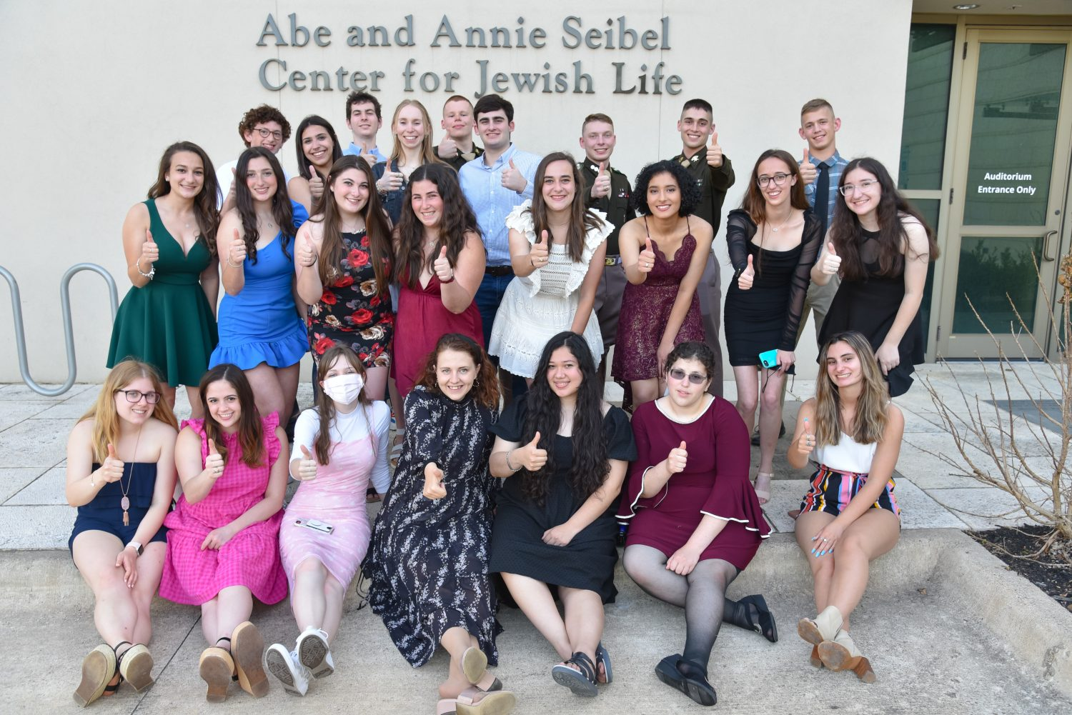 A group picture of students dressed up doing the gig em symbol